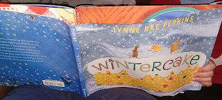 several small animals walk atop a fruitcake against a snowy background on the book Wintercake by Lynne Rae Perkins