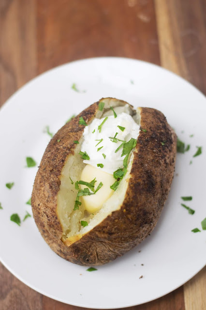 The baked potato on a white plate with butter and sour cream.