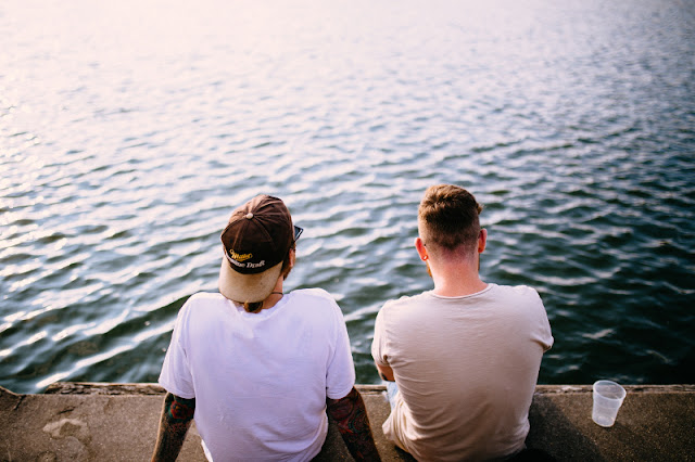 Two friends hanging out, sat looking out into the ocean