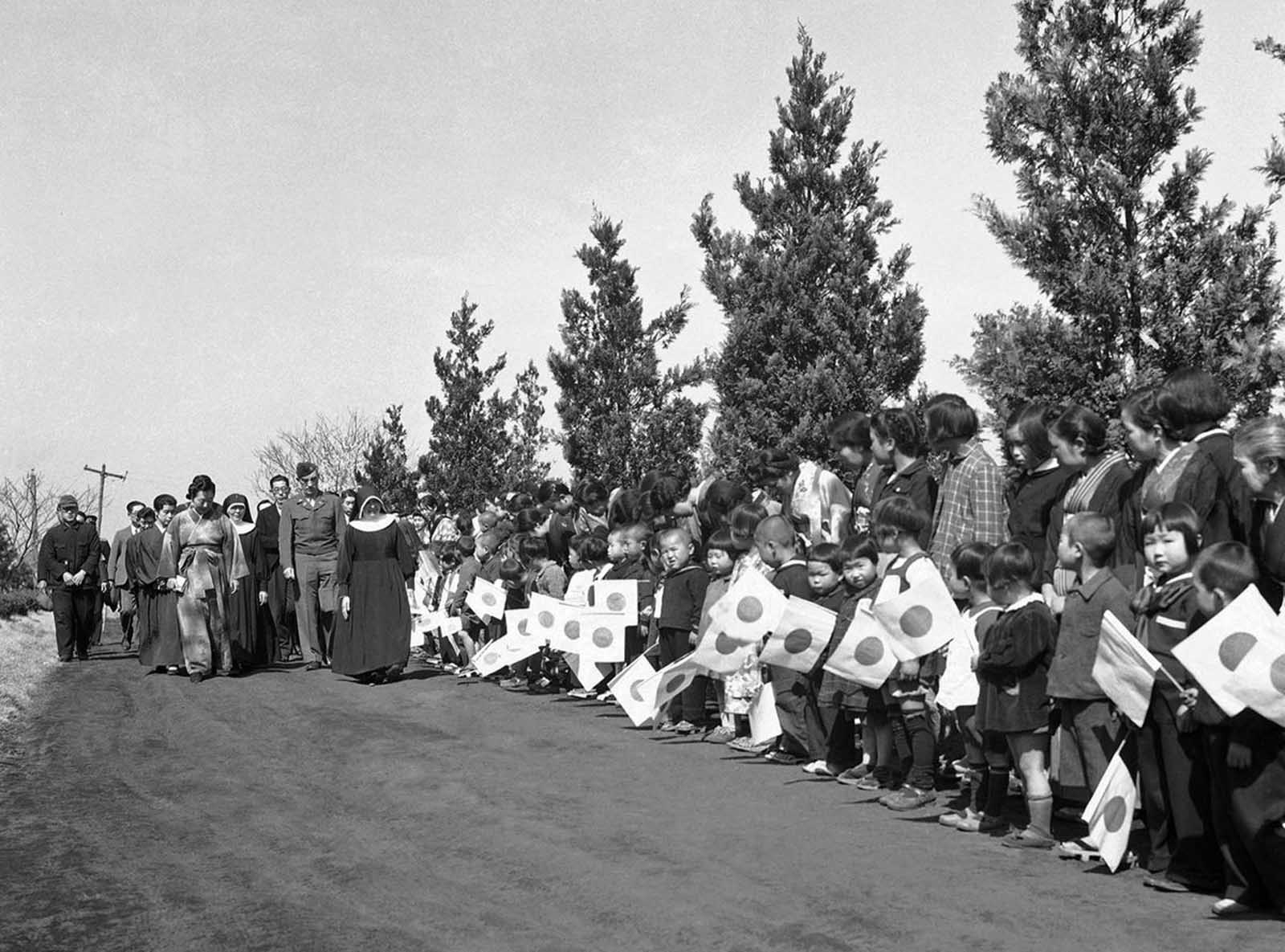 The Empress of Japan visits a Catholic Orphanage staffed by Japanese Nuns for children who have lost their parents in the war and air raids over Tokyo. The Empress inspected the grounds and paid a visit to the chapel. Children wave Japanese flags to greet the Empress during her visit in Fujisawa in Tokyo, on April 13, 1946.