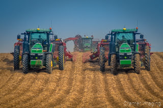 Photograph of John Deer tractors harvesting potatoes from a potato field in Aberdeen Idaho as taken by Cramer Imaging