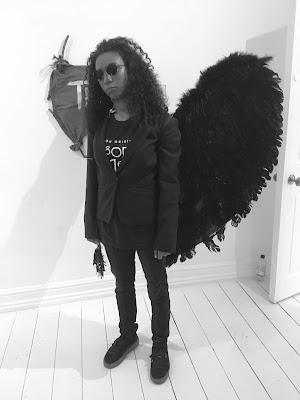 blck and white photo of a young woman dressed in black and wearing dark glasses and black feathered wings