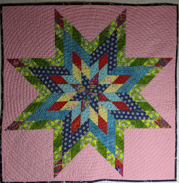 Printed cotton in three shades of blue, two shades of green, red, and yellow form a modern Lone Star that rests on a bright pink background.