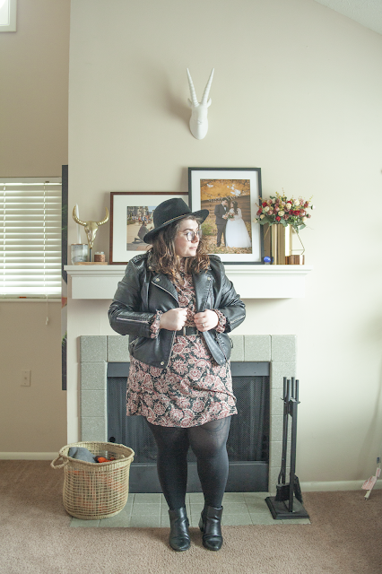 An outfit consisting of a black wide brim hat, a black faux leather moto jacket over a paisley peter pan collar shirt dress and black chelsea boots.