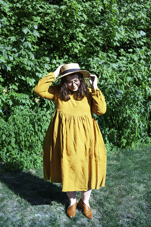 An outfit consisting of a straw boater hat, mustard yellow long sleeve linen smock dress, and cognac d'orsay flats.