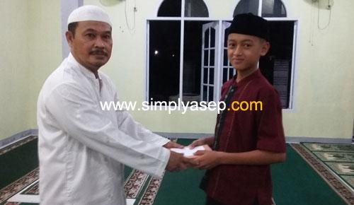 SIMBOLIS  : H. Rudyanto Putro, Ketua Pelaksana Pembangunan Masjid Babussalam mmberikan hadiah secara simbolis kepada salah seorang peserta Khataman Al Quran malam itu. Foto Asep Haryono