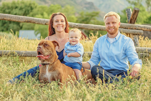 a family poses in a grassy meadow in Golden Colorado for their family portraits