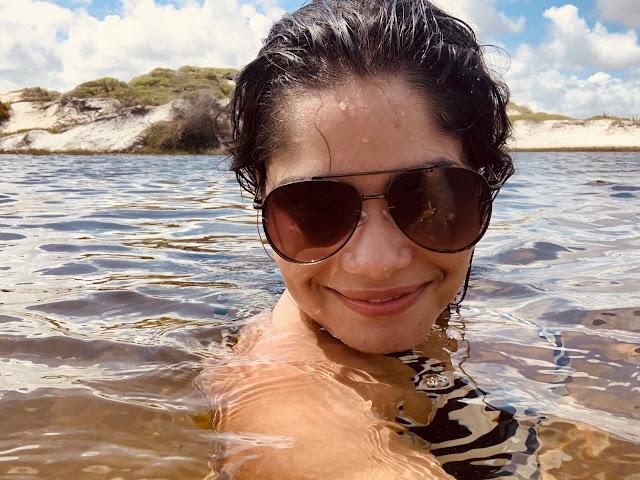 mulher jovem de cabelo preto e oculos escuros mergulhando em uma lagoa