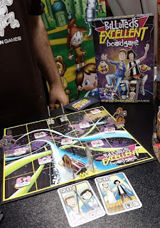 A photo of the game board with pieces on it mid-play. The board is a five-by-five grid on a background of cartoon-style artwork of the temporal pipelines from the Bill & Ted Movies. Tokens representing the historical characters are stacked around the board. The player's pieces are cardboard tiles of phone booths with an arrow to indicate facing, standing in a plastic base. An employee of Steve Jackson Games can be seen standing next to the table on which the game and the box are arranged.
