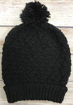Black beanie hat with pompom knitted with seersucker stitch