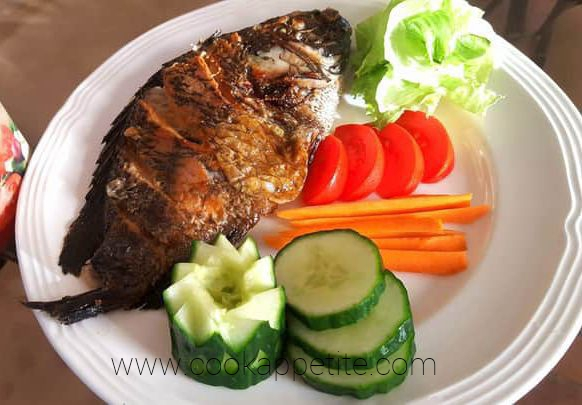 Fried Fish With Cucumber, Cabbage, Carrots And Tomato Salads