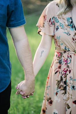 Pareja tomada de la mano, ella con un vestido cruzado y con flores