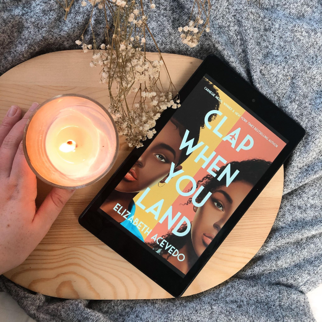 Cover of 'Clap When You Land' by Elizabeth Acevedo next to a candle and baby's breath flowers