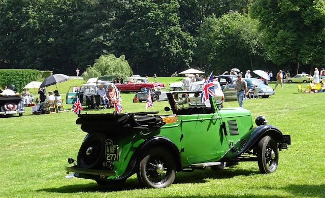 Grünes Oldtimer Cabrio mit englischen kleinen Flaggen auf dem Rasen des Schlossparkes auf dem 1. Fashionaward