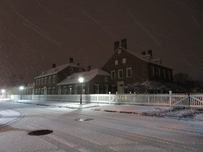 View of large two-story brick house. The street in front is covered in snow and a street light shows snow is still falling.