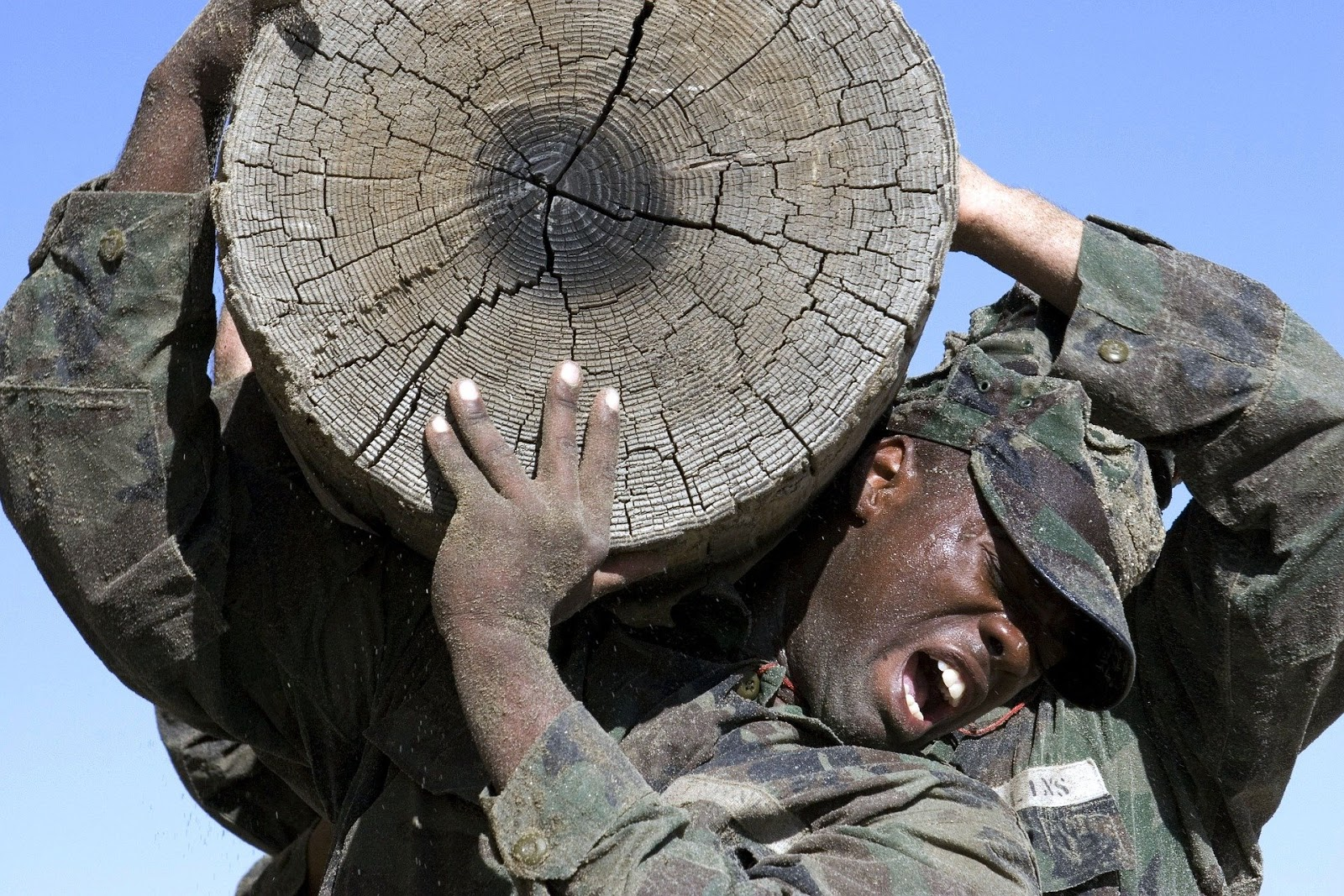 close up of soldiers carrying a large log on their soldiers to illustrate a blog post about tv show surviving the cut