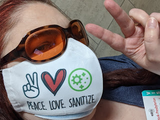 Close photo of me holding my hand up in a peace sign, wearing a mask that reads PEACE, LOVE, SANITIZE
