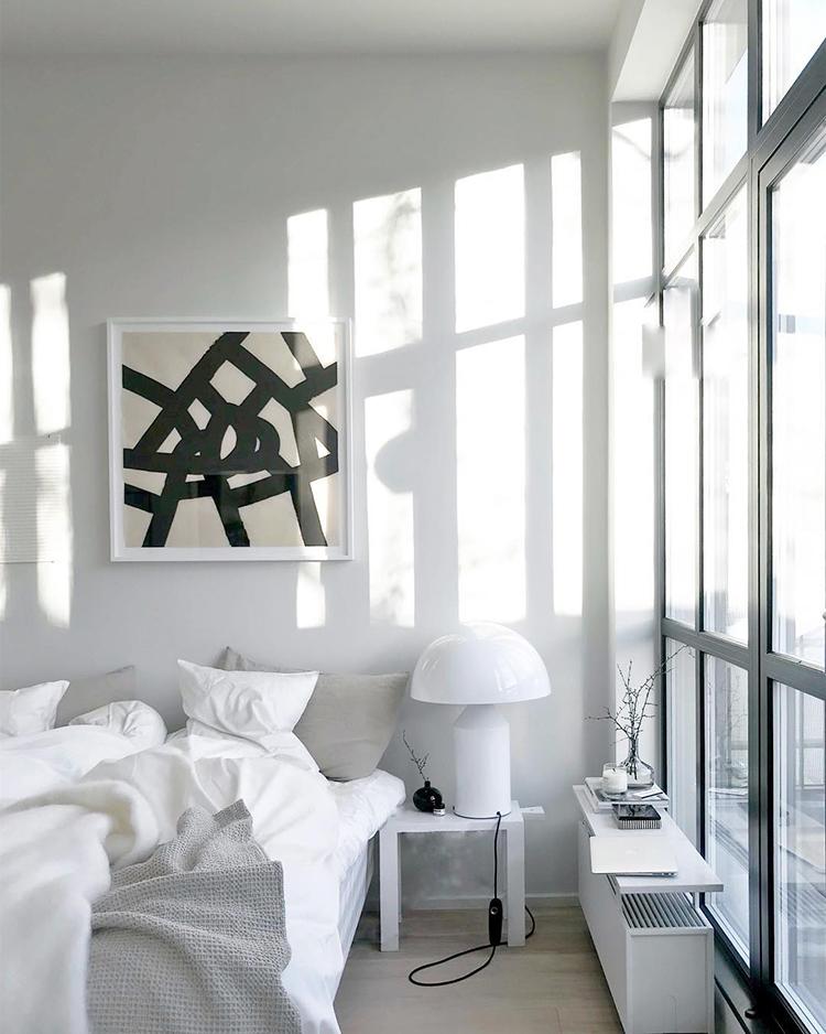 White bedroom with large window. Image via Lotta Agaton Interiors on Instagram