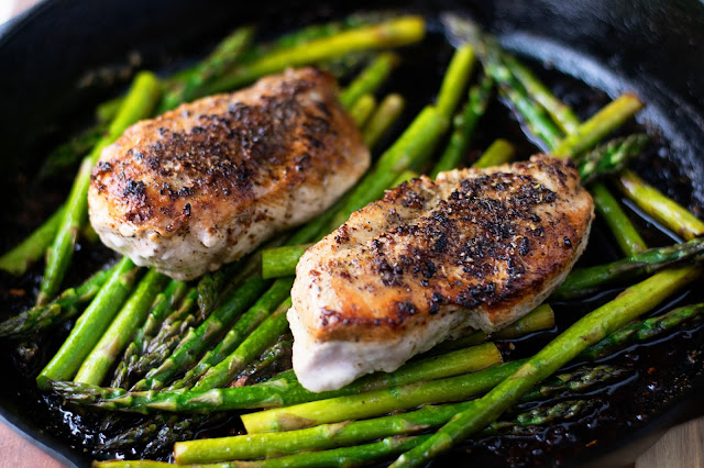 The fully cooked garlic and herb chicken with the asparagus in the pan.