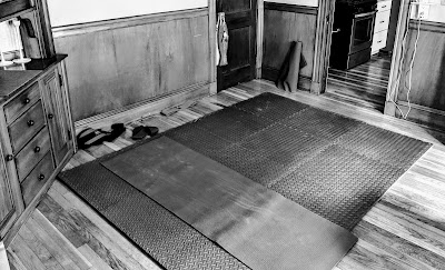 A black and white photo of a room in a house with wooden floors and a large 9 by 9 feet mat on the floor