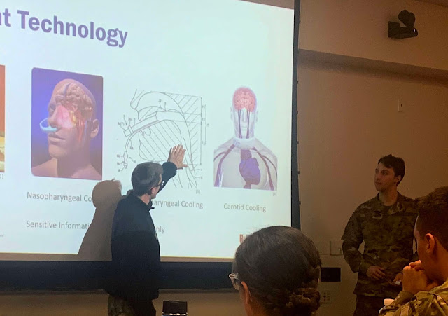 ENS Michael Goldstein, now president of the Medical Innovations Interest Group, points to a slide about a carotid cooling technique. He and 2nd Lt. Conrad Dear, current vice president of the group, on the right, recently presented their innovative concept to a panel of USU faculty members and physicians to gain feedback on whether their project would be ready for the next phase of development. (photo by Sarah Marshall)
