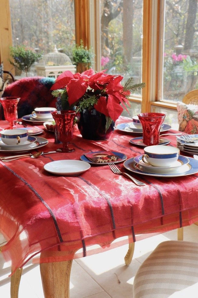 Deep navy stripes of soft velvet contrast with sheer red fabric used as a beautiful Christmas tablecloth