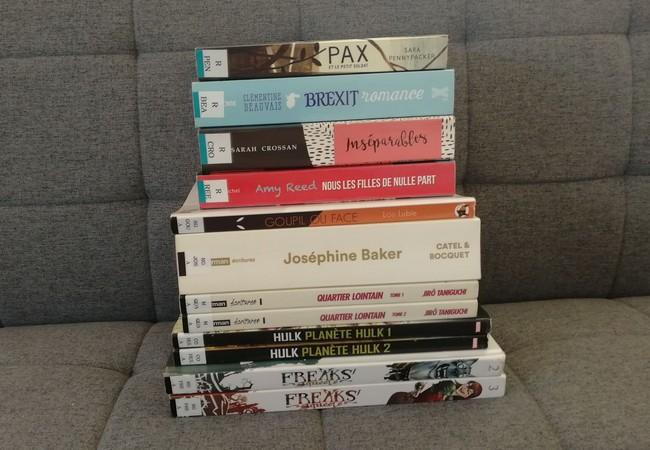 Tous les livres empruntés posés les uns sur les autres sur un canapé gris