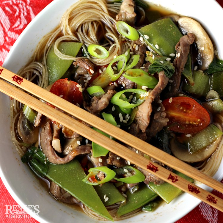 Overhead view of a bowl of Spicy Chinese Beef Noodle Soup by Renee's Kitchen Adventures with a set of wooden chopsticks over the top of the bowl of soup