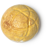 A spherical gold bath bomb with intricate squiggles engraved into tt with gold glitter on a bright background