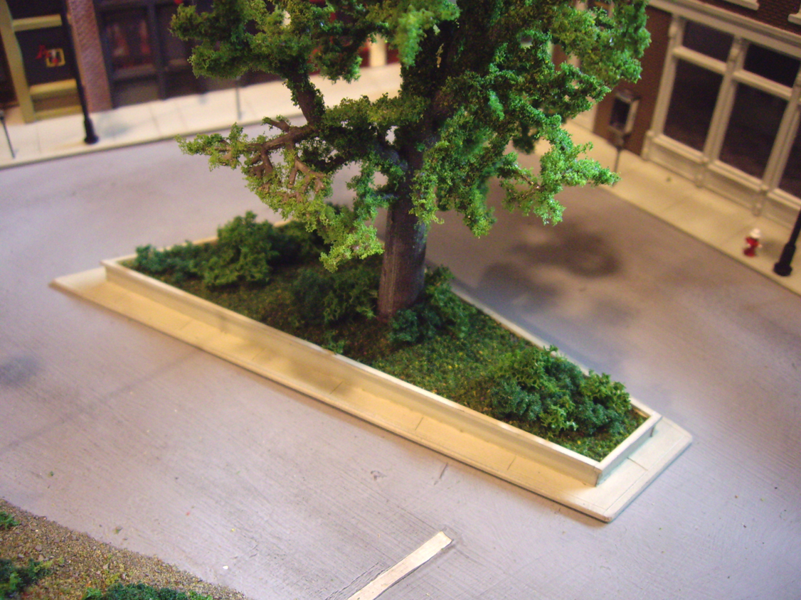 A scratch built center median complete with trees, ground foam and placed in the center of a downtown scene