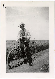 Lot 045 v1p17.1, View of Edgar Syverud with his bicycle and a camera in hand