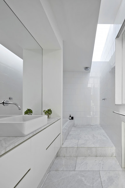 Bath room with white stone flooring, white tale walling, clean bath room.