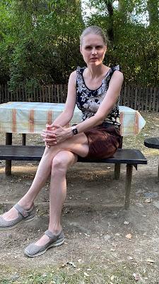 Linda sedí na lavici u stolu