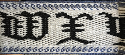 A photo of a section of tablet woven band with the letters W and X in black on a white background