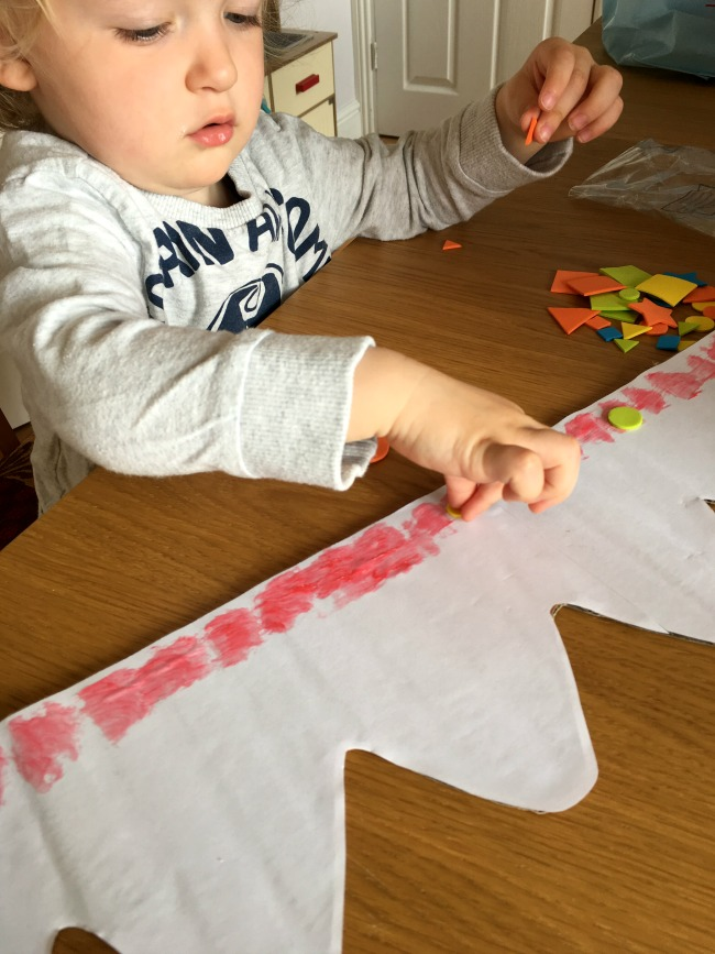 toddler sticking foam shapes onto paper crown