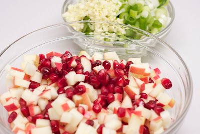 green onions and garlic  on a bowl and diced apple and pomegranate seeds  on another bowl