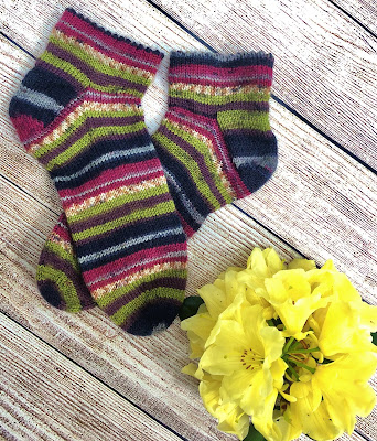 Socks knitted topdown picot edge with DROPS Fabel Candy and yellow rhododendron flowers
