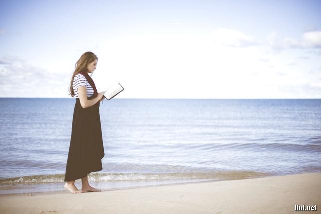 ảnh người phụ nữ vừa dạo biển vừa đọc sách