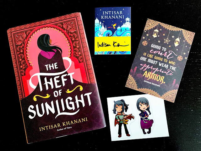 On a black background, we see The Theft of Sunlight hardcover on the left, with several items to the right: a signed bookplate, a quote postcard, and character stickers
