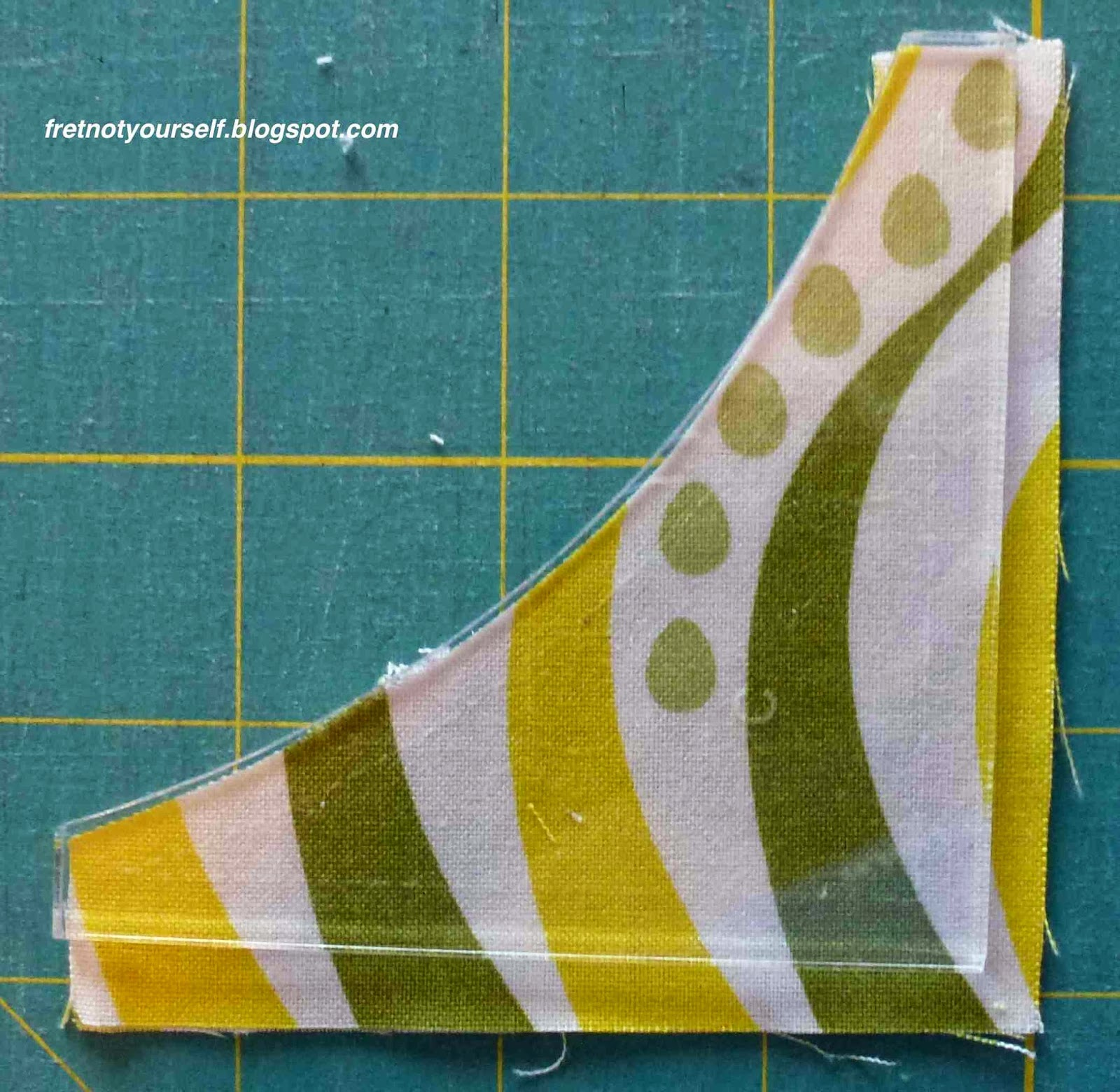 Plastic template is positioned on fabric to show how larger outer seam allowance was cut.