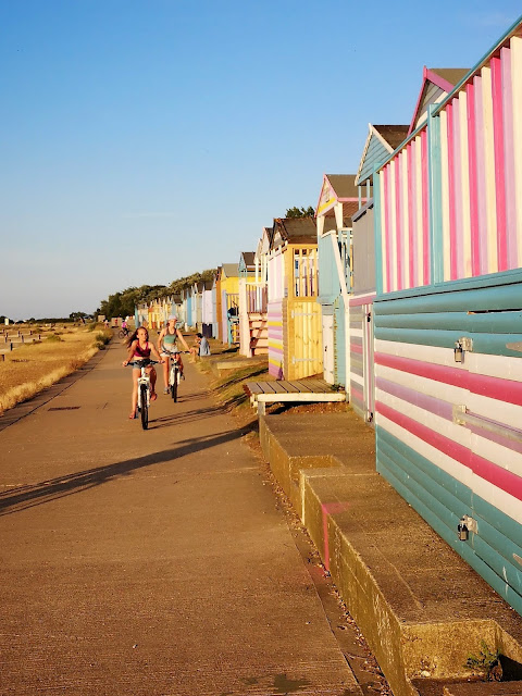 Cycling on the prom by colourful beach huts