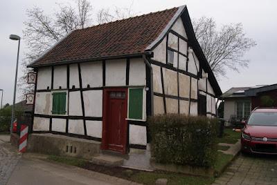 Ein kleines, schiefes Fachwerkhaus mit einer roten Tür und grünen, geschlossenen Fensterläden