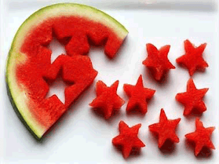 A piece of watermelon with stars cut out of it and spread around