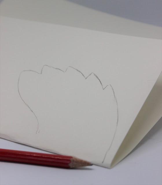 Das weiße Papier ist gefaltet und ein Engelsflügel ist darauf gemalt.