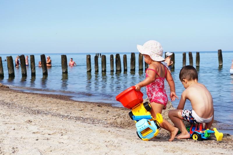 dzieci bawią się na plaży, co zabrać na wakacje, lista
