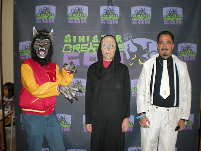 "Three convention attendees in costume: Michael Jackson ""Thriller"" Werewolf, ""Old Man"" in a cloak, and a ""Pimp""."