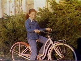 Ann Gotlib | a young girl wearing blue jeans and a blue jacket sitting on a bicycle with her red hair pulled into a ponytail | True Crime | mommalovestruecrime.com