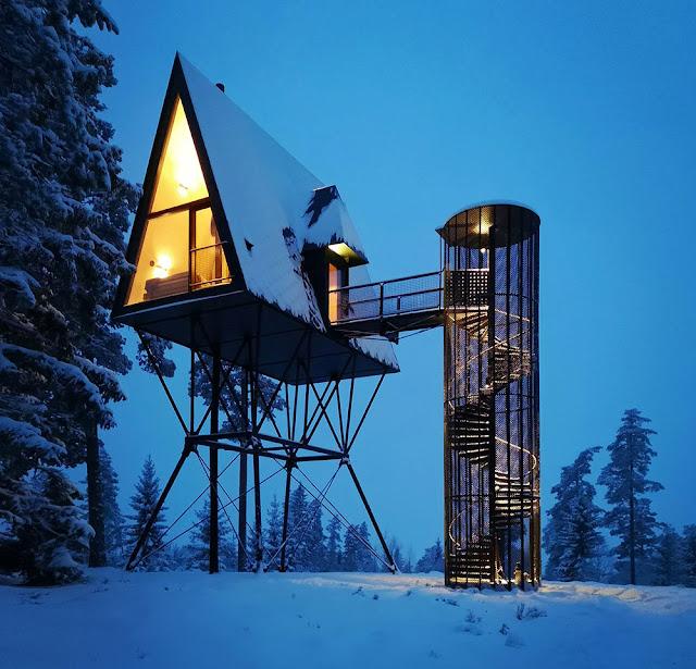 vista nocturna de la cabaña con luz cálida interior y nieve al exterior