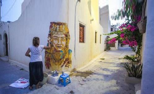 سيدة من سكان جربة تقوم برسم جدارية للملكة الأمازيغية تيهيا