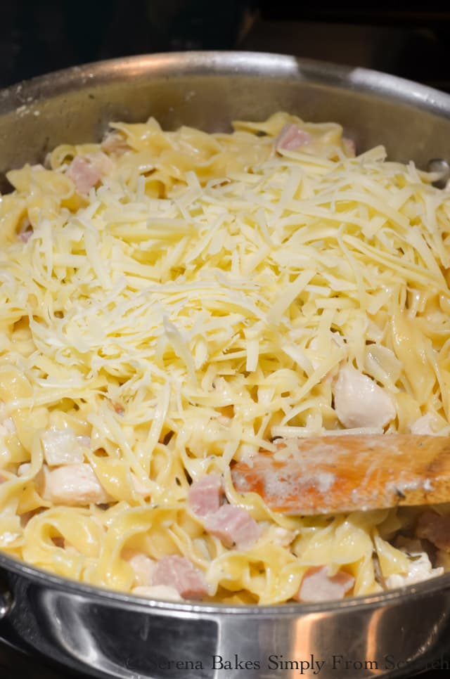 Grated Gruyere Cheese over the top of cooked noodles with ham and chicken in a stainless steel sauté pan.